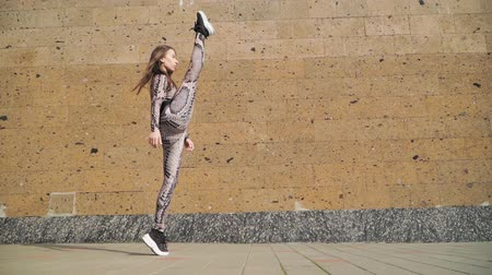 perna : Young Beautiful Athletic Girl Gymnast with Steep Stretch. She goes and does leg in split. Dressed in her slinky jumpsuit with picture scales Cobra. On a brown background concrete wall. Slow motion