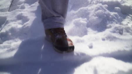 buty : Close-up. Man walking on snow brown winter boots and gray sweatpants.