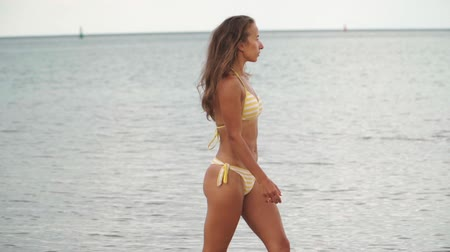 flee : Beautiful athletic girl in the yellow swimsuit is on the beach along the sea.