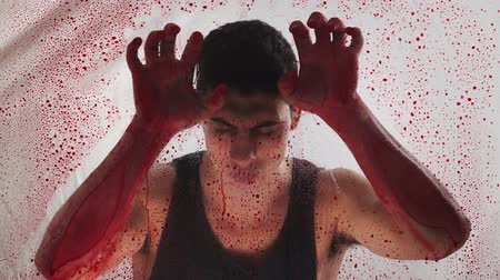 matança : The guy covered in blood standing behind the transparent glass with red droplets. Bloody hands of a killer psychopath. Close-up