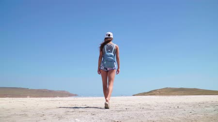 algler : A girl walks along the beautiful kayash pink salt lake in Crimea. Slow motion Stok Video