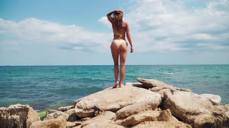 sedutor : Beautiful athletic Caucasian girl in the yellow bathing suit goes over rocks sea Stock Footage