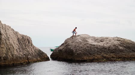 bergbeklimmer : Young athletic guy traveler who climbs on rocks in the sea. Slow motion.