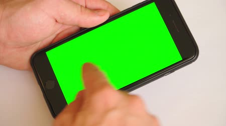 conserva : guy holding a smartphone in the hands of green screen, hand of man keeps mobile smart phone with chroma key. on white background