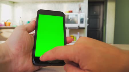 conserva : guy holding a smartphone in the hands of a green screen, hand of man keeps mobile smart phone with chroma key. Stock Footage