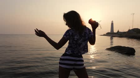 gracefully : girl dancing background of the sea and sunset with a music column in his hands