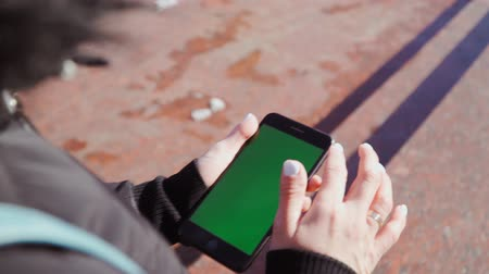 érintőképernyő : girl holding a smartphone in the hands of a green screen and goes down the street climbing in the phone. Shooting on steadicam