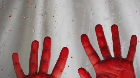 vražda : Bloody hands white background. Behind a transparent glass covered with red drops