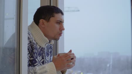 задумчивый : Caucasian guy drinking tea from a mug standing at the window in winter weather Стоковые видеозаписи