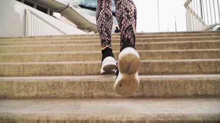 klatka schodowa : Close-up. The girl runs up the stairs. She is wearing black athletic sneakers and leggings. Slow motion