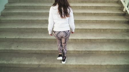 lépcsőház : A young girl in a white jacket and leggings up the stairs. Top view