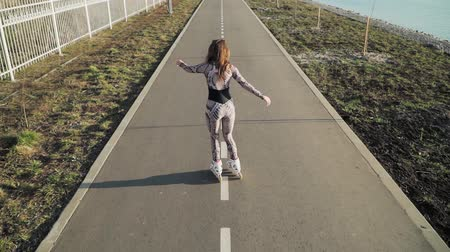 delgado : Athletic slender girl rollerblading on the path along the lake. Slow motion. Top view. Shooting on the steadicam Vídeos