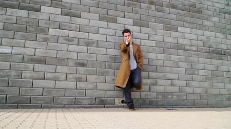 позирует : Beautiful young fashionable guy standing beside the concrete wall in the city Park. On it wearing a long brown coat. Slow motion. Shooting on the steadicam