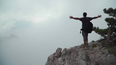 rucksack : The guy comes to the edge of the mountain and raises his hands up. At the height of bird flight. Slow motion Stock Footage