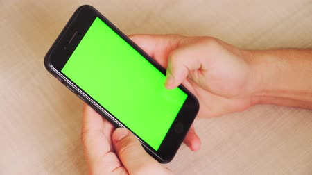 conserva : guy holding a smartphone in the hands of a green screen, hand of man keeps mobile smart phone with chroma key. on white background