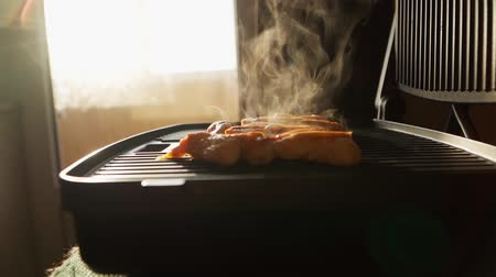grillowanie : Cooking fried chicken meat on an electric grill. Beautiful sunlight on the background. Good nutrition. Slow motion. Close up