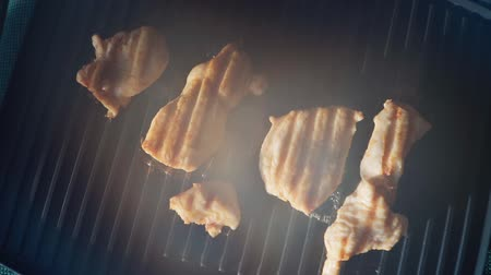grillowanie : Cooking fried chicken meat on an electric grill. Beautiful sunlight on the background. Good nutrition. Slow motion. Close up. Top view