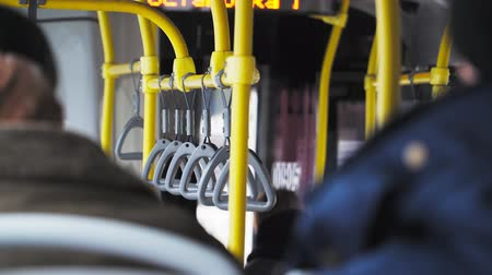inside bus : Close up. people inside public transport bus. Handrails to hold