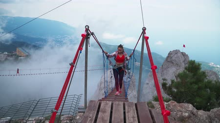 lano : Young athletic girl is a traveler crossing the Rope bridge above the precipice in the mountains. Slow motion