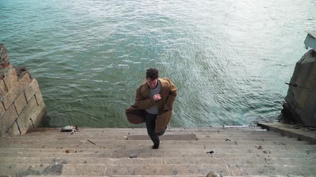 hevesli : Happy Young Man Actively Dancing While Walking up the stairs. Hes Wearing a brown long coat. Scene Shot in an Urban Park on the background of the river. Slow motion. Shooting on steadicam