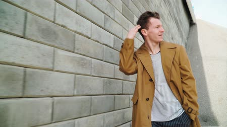 o : Stylish Beautiful Young Happy Caucasian Guy Goes along the City Wall and smiles. He is dressed in a Brown Long Coat. Close up Stok Video