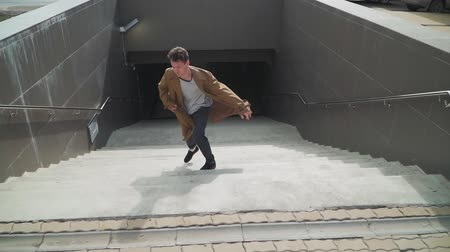 hevesli : Happy Young Man Actively Dancing While Walking Rises up the stairs from the underpass. Hes Wearing a brown long coat. Scene Shot in an Urban Park Next to Business Center. Slow motion. Top view
