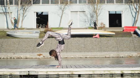 アクロバティック : Young athletic female gymnast performs handstand, on the pontoon near blue lake. Slow motion 動画素材