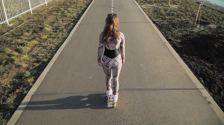 bruslení : Athletic slender girl rollerblading on the path along the lake. Slow motion. Top view. Shooting on the steadicam Dostupné videozáznamy