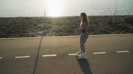 bruslení : Athletic slender girl rollerblading on the path along the lake and a beautiful sunset. Slow motion. Top view. Shooting on the steadicam