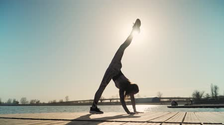 растягивание : young athletic girl with a great stretch is the splits on on the background of a beautiful sunset and lake. Slow motion Стоковые видеозаписи