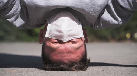 baktériumok : Guy in a medical mask on upside down. The world has gone crazy due to the coronavirus. Turned on its head. Portrait. close-up. Slow motion Stock mozgókép
