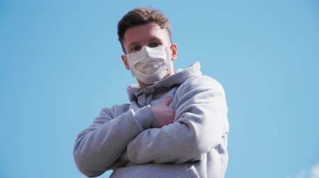 baktériumok : Young Caucasian guy in a medical mask stands. COVID-19 or coronavirus 2019 concept. Slow motion 4K
