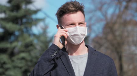 baktériumok : Guy in a medical mask wearing a jacket goes and talking on the phone. COVID-19 or coronavirus 2019 concept. Slow motion 4K