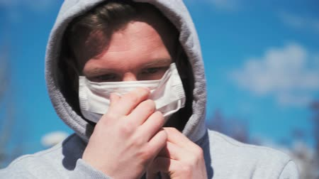 baktériumok : A young guy in a gray hoodie wears a medical mask on the face. Close-up portrait. COVID-19 or coronavirus 2019 concept