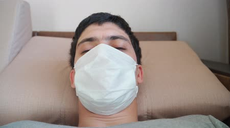 baktériumok : Guy in a medical mask looking at the camera. He lies on the sofa and falls asleep. COVID-19 or coronavirus 2019 concept