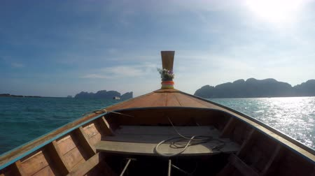 ilk : A first person view on a traditional wooden Thai motorboat  a longtail boat  Ruea Hang Yao. Going from Phi Phi Don Island to Maya Bay on Phi Phi Leh looking out over the ocean and the limestone islands sticking up from the water.  With sound. Shot in 4k U Stok Video
