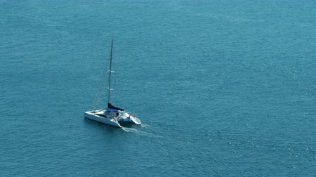 cascos : A catamaran Hobie Cat sailboat twin hulls is sailing on a beautiful open ocean.   This is the 30p sped up timelapse version.
