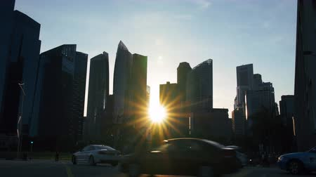 kerület : A timelapse of the sun setting between the skyscrapers in the financial  central business district of the city of Singapore. You see traffic go by as the sun sets and night falls. Stock mozgókép
