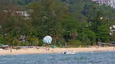 KARON BEACH, THAILAND - APRIL 24 2015 - Tourists are walking on Karon Beach and a boat ready to take people parasailing is anchored close to the beach. Stock Footage