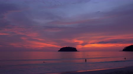закат : Silhouettes of people swimming in a warm tropical ocean right after sunset. The sky is amazing with purple and orange colors.