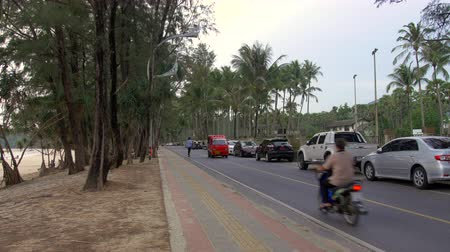 PHUKET, THAILAND - APRIL 25 2015 - People riding bicycles and skateboarding with traffic on Kata Road in Phuket, Thailand right before sunset. Stock Footage