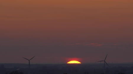 ветроэнергетики : A big sun sets over Sweden and Denmark and wind turbines, or wind power stations, spin while creating sustainable energy for the area. Fast timelapse. Filmed from Lund, Sweden, overlooking Copenhagen, Denmark.
