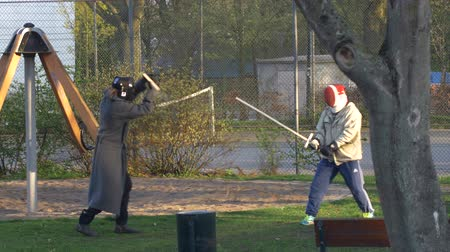 SCANIA, SWEDEN - MAY 2015 - Two masked persons are practicing sword fighting with wooden swords for a cosplay event. Stock Footage