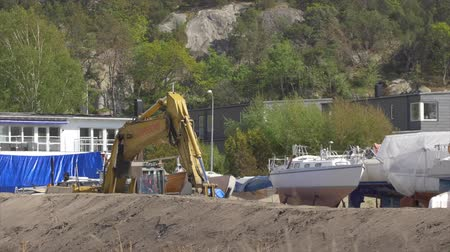 GOTHENBURG, SWEDEN - MAY 2015 - An excavator is working at a construction site by a marina with boats on land. Location: Brottkarr, Gothenburg, Sweden.