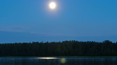 fullmoon : A time lapse of the full moon moving close to an island in a Swedish lake in the middle of summer. With beautiful reflections in the water. Location: Pitea, Sweden Norrbotten in July. Stock Footage