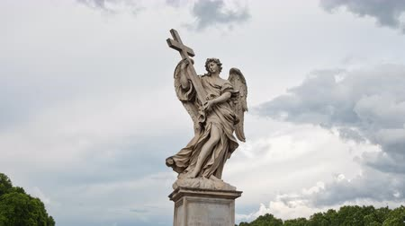Time lapse with clouds behind the Angel with the Cross closeup on the Bridge of Hadrian (Ponte Sant'Angelo) in Rome, Italy. 4k resolution.  Sculptor: Ercole Ferrata. Stock Footage
