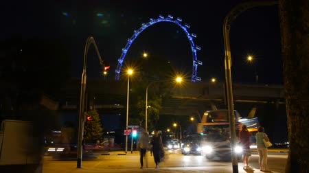 SINGAPORE, APRIL 2015 - Time lapse of the Temasek Avenue and Raffles Avenue crossing in Singapore near the Marina Bay Sands Hotel. People are crossing the street and many cars are driving by. You also see the Singapore Flyer ferris wheel.