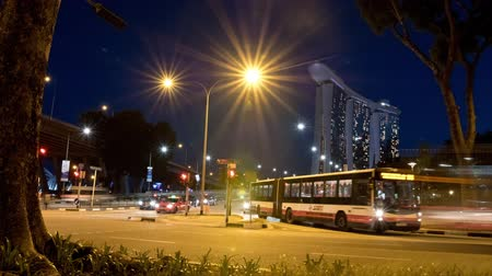 SINGAPORE, APRIL 2015 - Time lapse of the Raffles Avenue and Bayfront Avenue crossing in Singapore near the Marina Bay Sands Hotel. People are crossing the street and many cars are driving by. Stock Footage