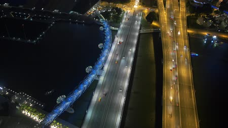 Cinemagraph of a magnificent aerial view of the Helix bridge and busy roads in Singapore at night. Time lapse sequence. Loopable motion background, only the ferry is moving. Traffic is frozen in time.