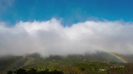 POV timelapse of clouds moving towards you with a beautiful colorful rainbow showing up at the bottom. Location: Top of Yangmingshan Mountain in Taipei, Taiwan. Amazing landscape weather first person perspective point of view.